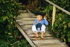 Όμορφο αγόρι στην ΚΑΠ και τις διόπτρες του που θέτουν τη συνεδρίαση σε μια ξύλινη γέφυρα Στοκ εικόνες με δικαίωμα ελεύθερης χρήσης