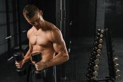 Όμορφο αθλητικό άτομο δύναμης bodybuilder που κάνει τις ασκήσεις στοκ εικόνα