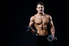 Όμορφο αθλητικό άτομο δύναμης που εκπαιδεύει αντλώντας επάνω τους μυς με τους αλτήρες σε μια γυμναστική Μυϊκό σώμα ικανότητας στο στοκ εικόνες