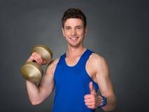 Όμορφο αθλητικό άτομο δύναμης στην κατάρτιση αντλώντας επάνω τους μυς με τους αλτήρες σε μια γυμναστική Στοκ Φωτογραφία