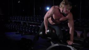 Όμορφο αθλητικό άτομο δύναμης στη γυμναστική που χρησιμοποιεί τον αλτήρα απόθεμα βίντεο