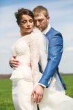 Όμορφο αισθησιακό παντρεμένο ζευγάρι που αγκαλιάζει στον πράσινο τομέα Στοκ Εικόνες