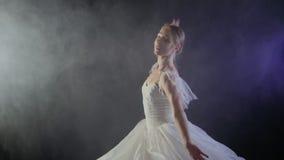 Όμορφο αισθησιακό ballerina στα άσπρα χορεύοντας στοιχεία φορεμάτων tutu του κλασσικού ή σύγχρονου μπαλέτου στο σκοτάδι με το φως απόθεμα βίντεο