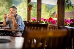Όμορφο ανώτερο άτομο που απολαμβάνει τον καφέ πρωινού του στοκ φωτογραφία
