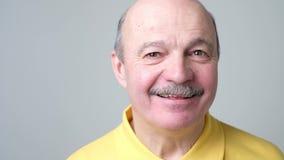 Όμορφο ανώτερο άτομο στο κίτρινο γέλιο μπλουζών φιλμ μικρού μήκους