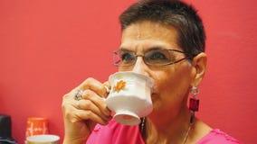 Όμορφο ανώτερο τσάι κατανάλωσης γυναικών στο άσπρο φλυτζάνι απόθεμα βίντεο