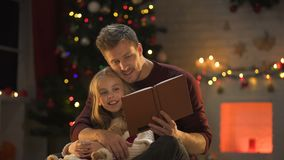 Όμορφο αρσενικό βιβλίο ανάγνωσης για το λατρευτό θηλυκό χριστουγεννιάτικο δέντρο παιδιών λαμπιρίζοντας πλησίον φιλμ μικρού μήκους