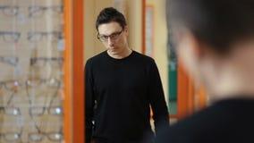 Όμορφο αρσενικό που δοκιμάζει eyeglasses στο οπτικό κατάστημα απόθεμα βίντεο