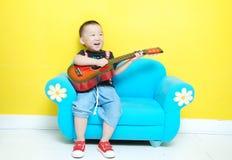 Όμορφο ασιατικό αγόρι με την κιθάρα στοκ εικόνες