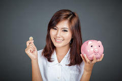 Όμορφο ασιατικό κορίτσι με ένα νόμισμα και ένα ρόδινο κιβώτιο χρημάτων χοίρων Στοκ Εικόνες
