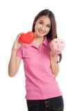 Όμορφο ασιατικό κορίτσι με την κόκκινη καρδιά και piggy τράπεζα Στοκ Φωτογραφίες