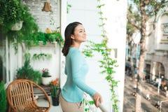 Όμορφο ασιατικό κορίτσι που απολαμβάνει τη φρεσκάδα στο μπαλκόνι Στοκ εικόνα με δικαίωμα ελεύθερης χρήσης