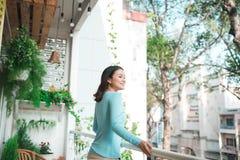 Όμορφο ασιατικό κορίτσι που απολαμβάνει τη φρεσκάδα στο μπαλκόνι Στοκ φωτογραφία με δικαίωμα ελεύθερης χρήσης