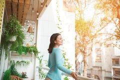 Όμορφο ασιατικό κορίτσι που απολαμβάνει τη φρεσκάδα στο μπαλκόνι Στοκ Εικόνες