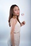 Όμορφο ασιατικό κορίτσι που κρατά ένα lollipop με τη χαρά Στοκ Εικόνες