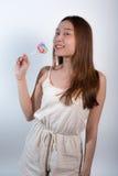 Όμορφο ασιατικό κορίτσι που κρατά ένα lollipop με τη χαρά Στοκ Φωτογραφία