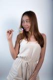 Όμορφο ασιατικό κορίτσι που κρατά ένα lollipop με τη χαρά Στοκ Φωτογραφίες