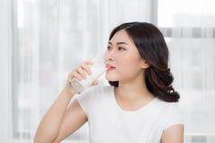 Όμορφο ασιατικό κορίτσι που πίνει ένα ποτήρι του γάλακτος Στοκ Εικόνα