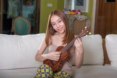Όμορφο ασιατικό κορίτσι που παίζει ukulele Στοκ Φωτογραφία