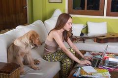 Όμορφο ασιατικό κορίτσι on-line ευτυχώς με το σκυλί Στοκ εικόνες με δικαίωμα ελεύθερης χρήσης