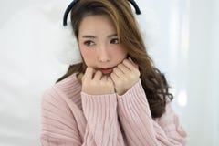 Όμορφο ασιατικό κρύο κοριτσιών που φορά τα άσπρα καλύμματα αυτιών και το θερμό sweate Στοκ Εικόνα