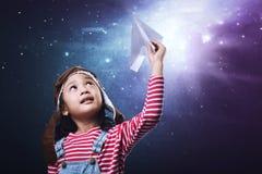 Όμορφο ασιατικό μικρό κορίτσι που έχει τη διασκέδαση με το παιχνίδι αεροπλάνων εγγράφου Στοκ Φωτογραφία
