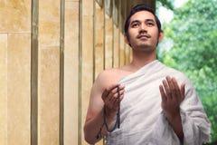 Όμορφο ασιατικό μουσουλμανικό άτομο με τις χάντρες προσευχής εκμετάλλευσης ihram Στοκ Φωτογραφίες