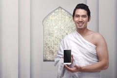 Όμορφο ασιατικό μουσουλμανικό άτομο που φορά ihram τα ενδύματα που κρατούν το κινητό π Στοκ Φωτογραφία