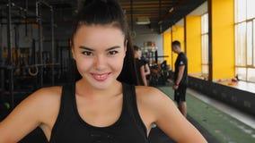 Όμορφο ασιατικό νέο κορίτσι στη γυμναστική που εξετάζει τη κάμερα και που χαμογελά μετά από να εκπαιδεύσει φιλμ μικρού μήκους