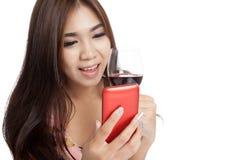 Όμορφο ασιατικό χαμόγελο γυναικών με το κινητό τηλέφωνο και το κόκκινο κρασί Στοκ φωτογραφίες με δικαίωμα ελεύθερης χρήσης