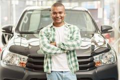Όμορφο αφρικανικό άτομο που επιλέγει το νέο αυτοκίνητο στον αντιπρόσωπο στοκ εικόνα