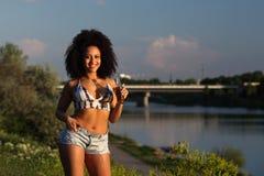 Όμορφο αφρικανικό κορίτσι με τη σγουρή τρίχα που στέκεται σε έναν ποταμό στοκ εικόνες με δικαίωμα ελεύθερης χρήσης