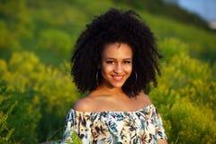 Όμορφο αφρικανικό κορίτσι με τη σγουρή τρίχα σε έναν τομέα των κίτρινων λουλουδιών στοκ εικόνες με δικαίωμα ελεύθερης χρήσης