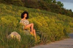 Όμορφο αφρικανικό κορίτσι με τη σγουρή τρίχα σε έναν τομέα των κίτρινων λουλουδιών στοκ εικόνα