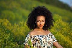 Όμορφο αφρικανικό κορίτσι με τη σγουρή τρίχα σε έναν τομέα των κίτρινων λουλουδιών Στοκ εικόνα με δικαίωμα ελεύθερης χρήσης