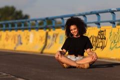 Όμορφο αφρικανικό κορίτσι με τη σγουρή τρίχα στην οδό στοκ εικόνες