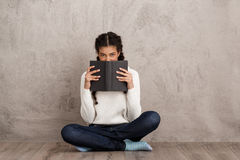 Όμορφο αφρικανικό κρύβοντας στόμα κοριτσιών πίσω από το βιβλίο πέρα από το μπεζ υπόβαθρο στοκ εικόνα με δικαίωμα ελεύθερης χρήσης