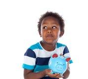 Όμορφο αφροαμερικανός παιδί με ένα μπλε moneybox Στοκ Εικόνες
