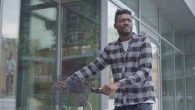 Όμορφο βέβαιο άτομο αφροαμερικάνων στα περιστασιακά ενδύματα που οδηγούν το ποδήλατό του κοντά στις προθήκες στην πόλη Ο τύπος απόθεμα βίντεο