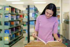 Όμορφο βιβλίο ανάγνωσης γυναικών στη βιβλιοθήκη στοκ εικόνες