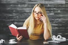 Όμορφο βιβλίο ανάγνωσης γυναικών στο γραφείο Στοκ Φωτογραφίες