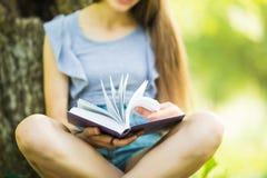 Όμορφο βιβλίο ανάγνωσης κοριτσιών στο πάρκο διαγωνισμός που προετο& Λογοτεχνικός ελεύθερος χρόνος υπαίθριος στοκ φωτογραφία με δικαίωμα ελεύθερης χρήσης