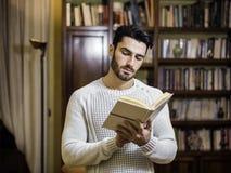 Όμορφο βιβλίο ανάγνωσης νεαρών άνδρων στο σπίτι στο καθιστικό του Στοκ Φωτογραφία
