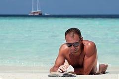 Όμορφο βιβλίο ανάγνωσης ατόμων στην άσπρη παραλία άμμου Στοκ φωτογραφίες με δικαίωμα ελεύθερης χρήσης