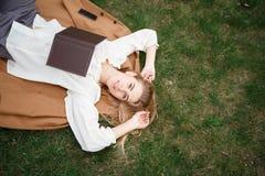 Όμορφο βιβλίο ανάγνωσης κοριτσιών στον κήπο ανθών μια ημέρα άνοιξη Στοκ Φωτογραφίες