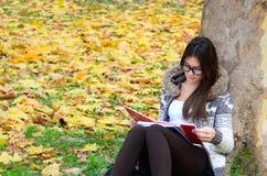 Όμορφο βιβλίο ανάγνωσης κοριτσιών brunette στη φύση Στοκ Εικόνες