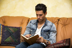 Όμορφο βιβλίο ανάγνωσης νεαρών άνδρων στο σπίτι, συνεδρίαση στον καναπέ Στοκ Εικόνα