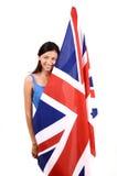 Όμορφο βρετανικό κορίτσι που χαμογελά κρατώντας ψηλά τη βρετανική σημαία. Στοκ Εικόνες