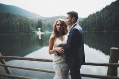 Όμορφο γαμήλιο ζεύγος που φιλά και που αγκαλιάζει κοντά στο βουνό με την τέλεια άποψη Στοκ εικόνα με δικαίωμα ελεύθερης χρήσης