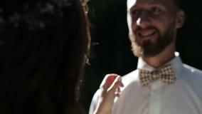 Όμορφο γαμήλιο ζεύγος στο φίλημα πάρκων στο ηλιοβασίλεμα φιλμ μικρού μήκους